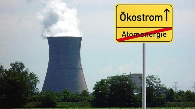 gefaktes Ortschild vor Kühlturm wirbt für Ökostrom statt Atomenergie