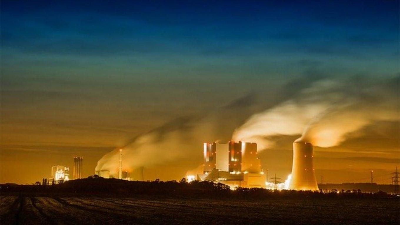 Rauchende Schlote und Kühltürme eines Kohlekraftwerks bei Nacht