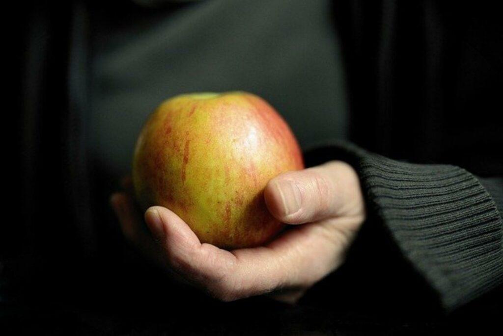 Hand hält einen Apfel