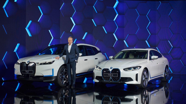 Konzernchef Zispe posiert vor den neuen vollelektrischen Modellen iX und i4