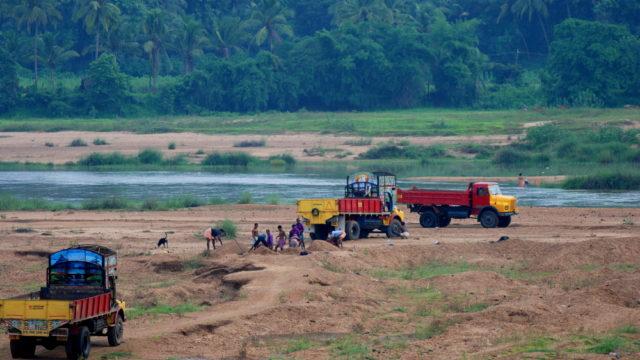 Per Lkw transportieren Arbeiter im indischen Bundesstaat Kerala Sand aus einem Flussbett ab