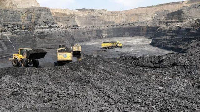 Bagger und Laster beim Kohleabbau in einer indischen Mine