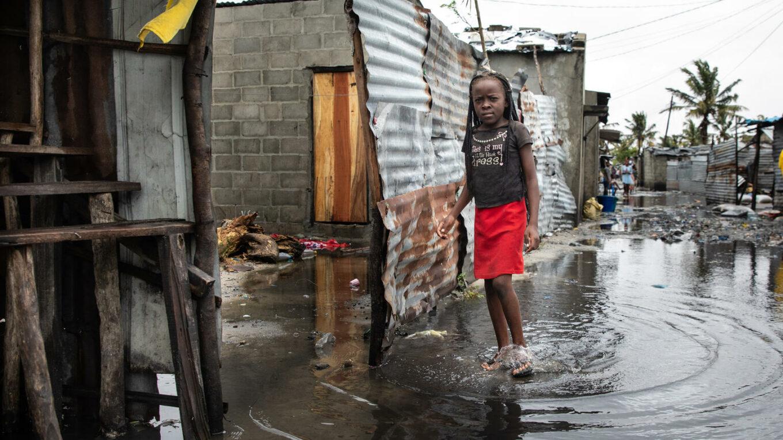 Jugendliche in einem überschwemmten Wohngebiet in Mosambik